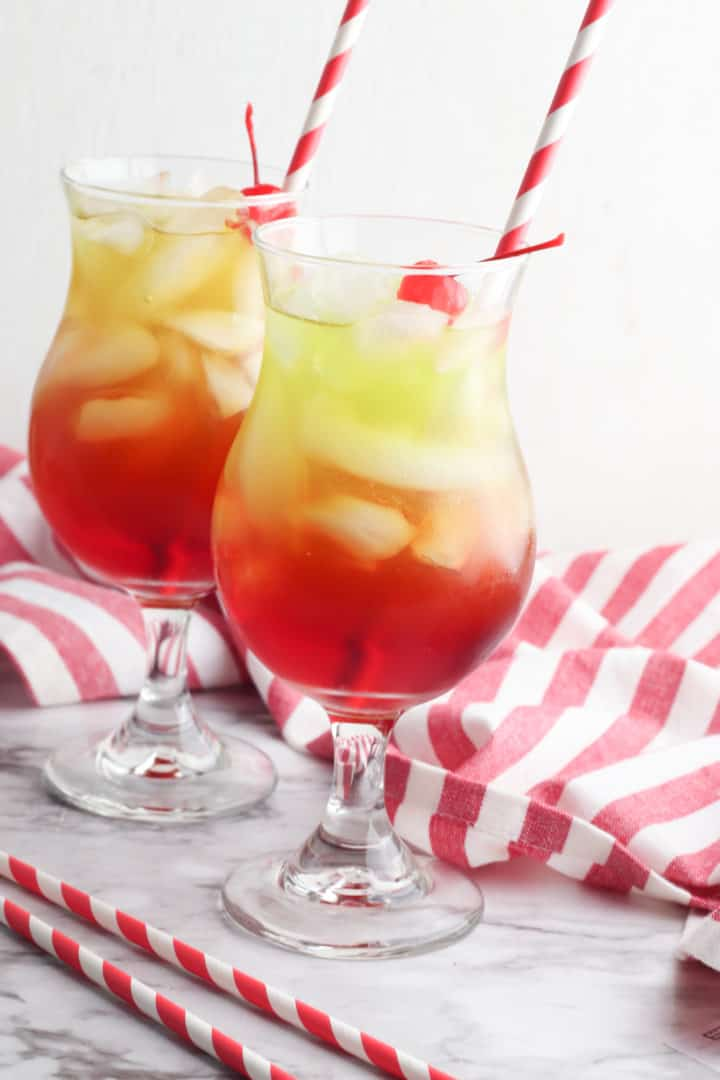 Christmas punch recipe in a glass with straws and a red striped napkin