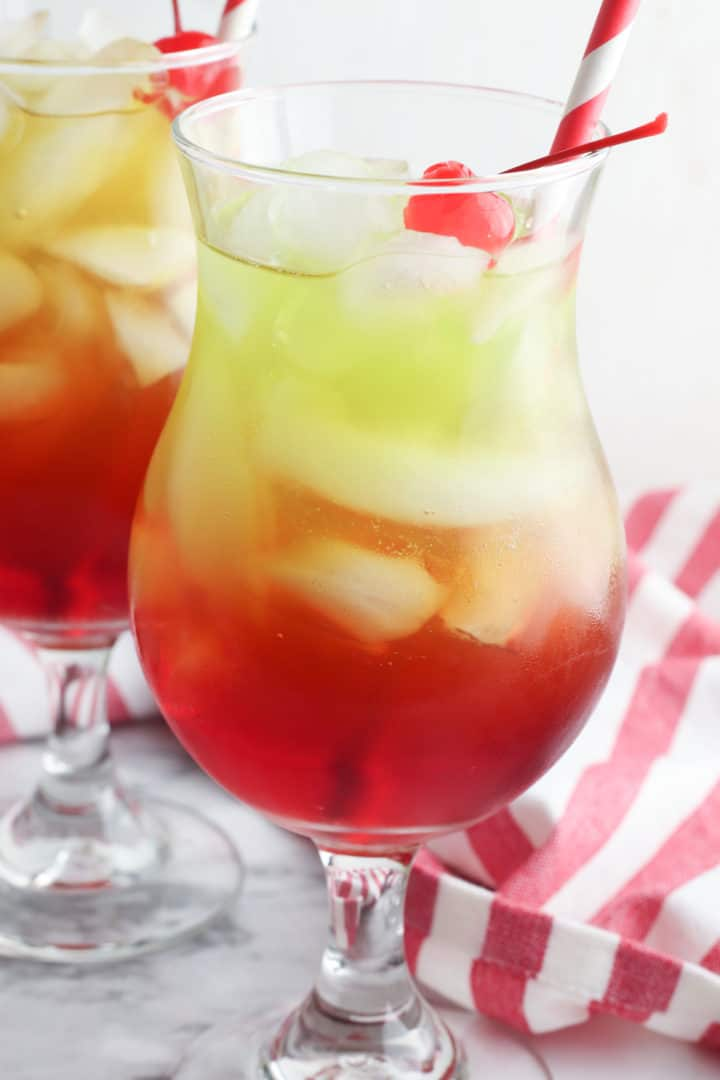 Non alcoholic Christmas punch in a glass with a straw and cherry on top