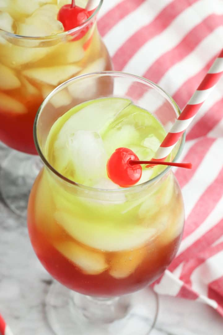 Christmas punch in a glass with a cherry on top and a red striped napkin on the side.