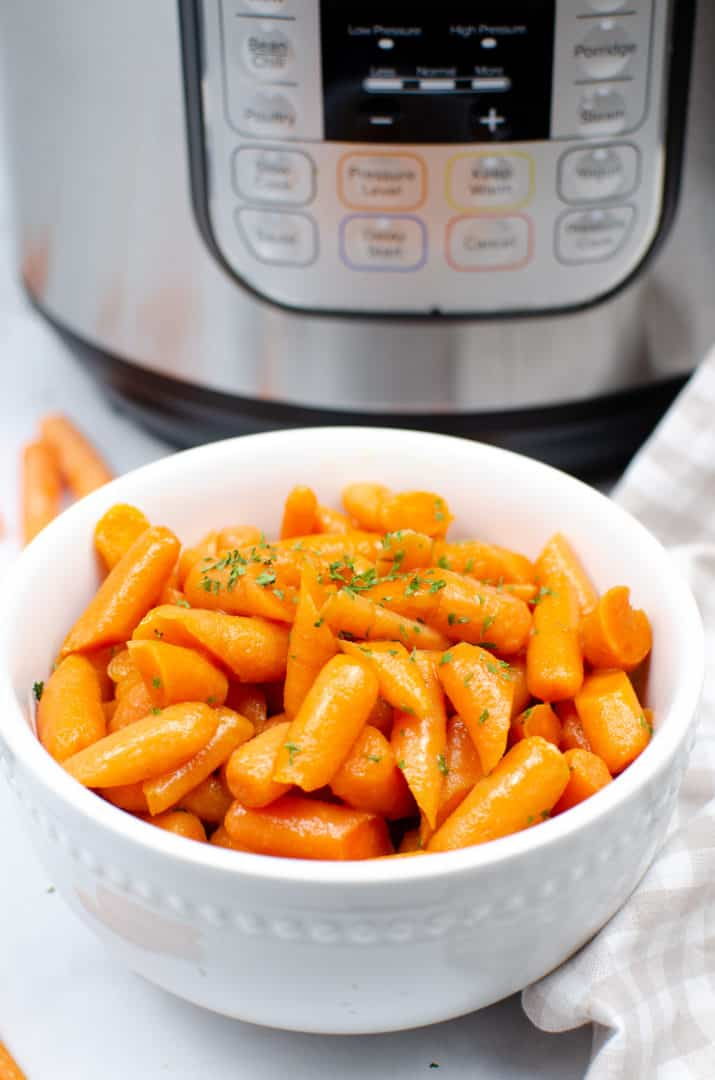 glazed baby carrots in a white bowl with an instant pot in the background