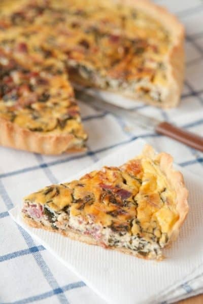 Ham, Cheese and Spinach Quiche on a plaid blue tablecloth