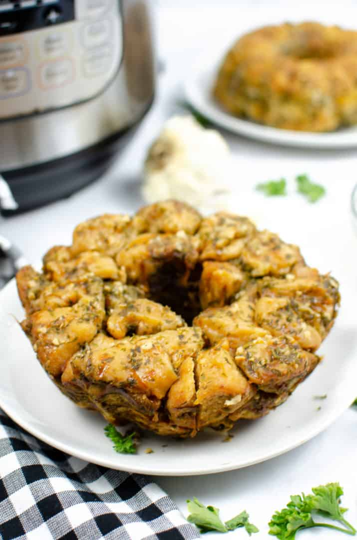 Instant pot garlic monkey bread recipe on white plate with a black checkered napkin and an instant pot in the background