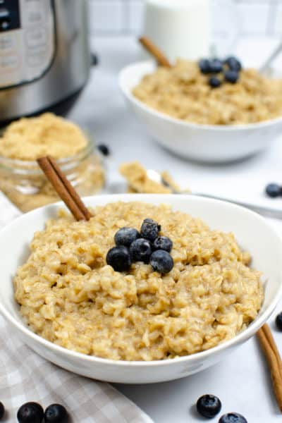 Instant Pot Maple and Brown sugarOatmeal in a white bowl with a cinnamon stick and blueberries