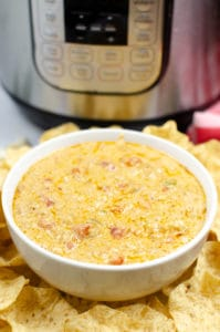 White bowl filled with Instant Pot Queso with Meat and surrounded by chips
