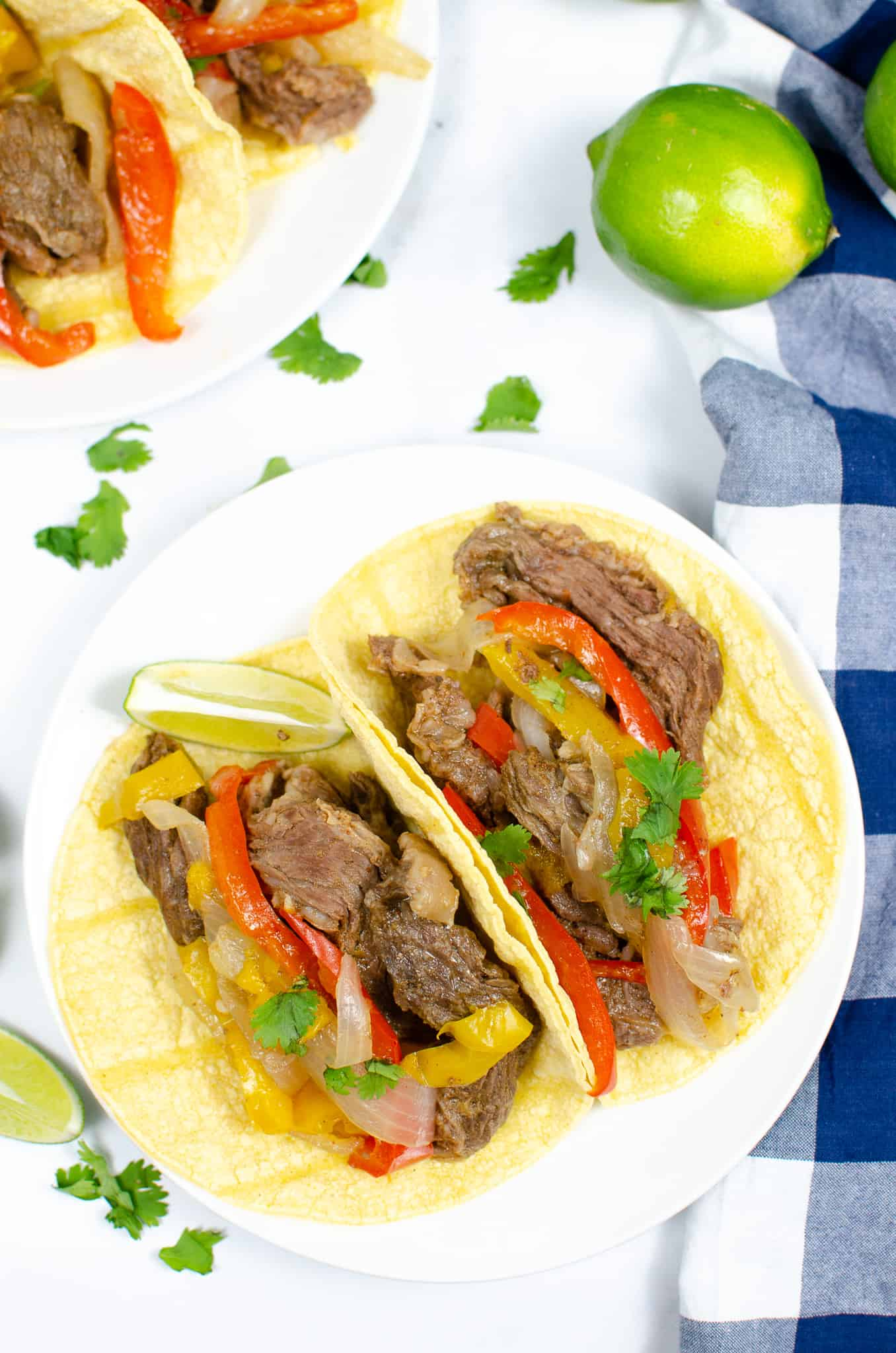 Steak Fajitas in shells on white plate with blue and white check napkin