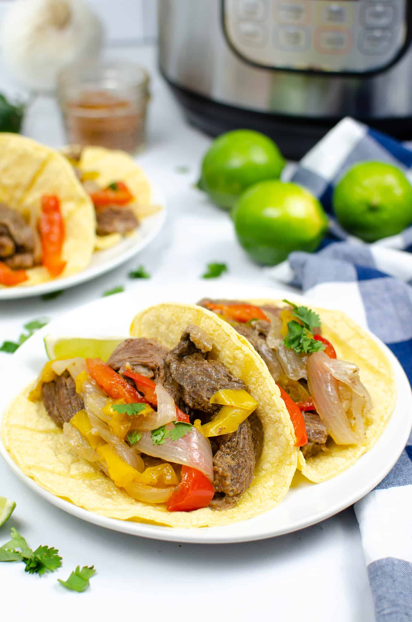 Instant Pot Steak Fajitas with limes and instant pot in background