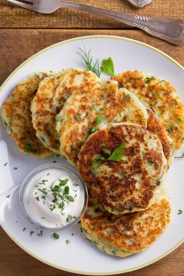 Mahed Potato Pancakes on a white plate with sour cream