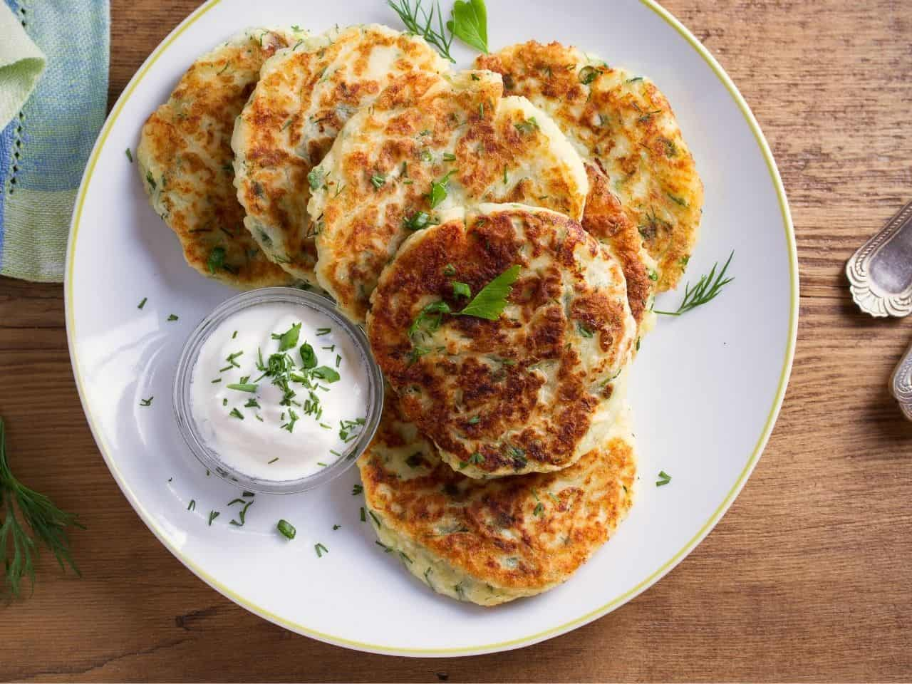 Potato Pancakes on a white plate with uellow trim on a wooden table