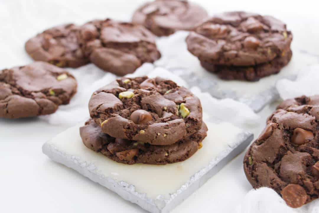 Several mint chocolate chip cookies arranged on a table with a white cloth