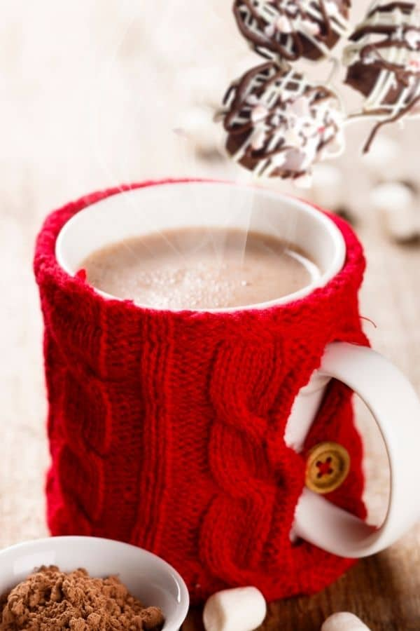 Peppermint Hot Chocolate Bombs with a steaming cup of hot cocoa in a red cozy.