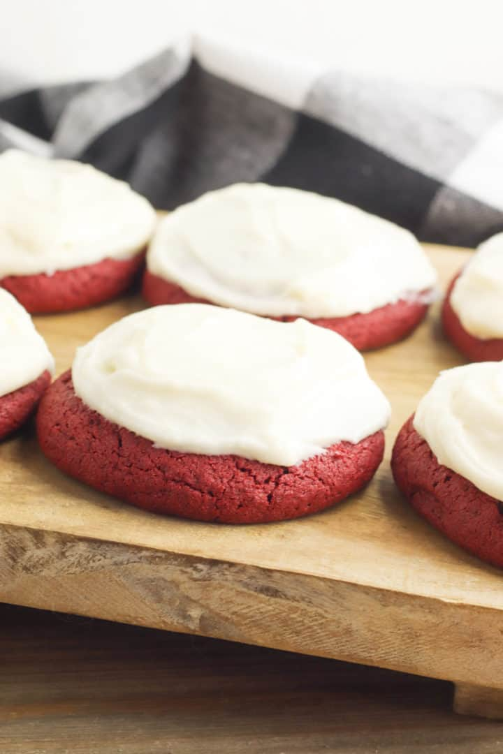 Red Velvet Cookies with buttercream frosting on a wooden board