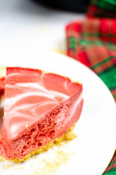 Instant Pot Cheesecake on white plate with red and green plaid napkin