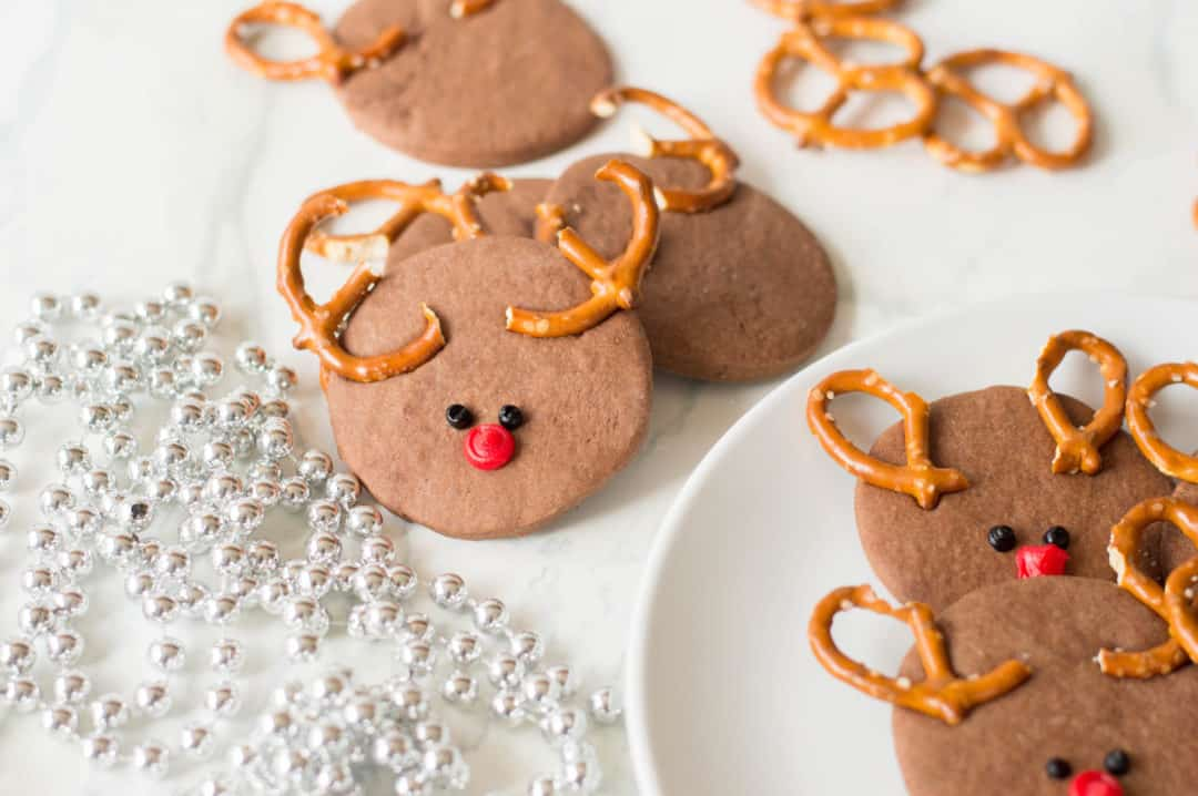 Reindeer cookies on a white plate with a string of silver pearls draped around.