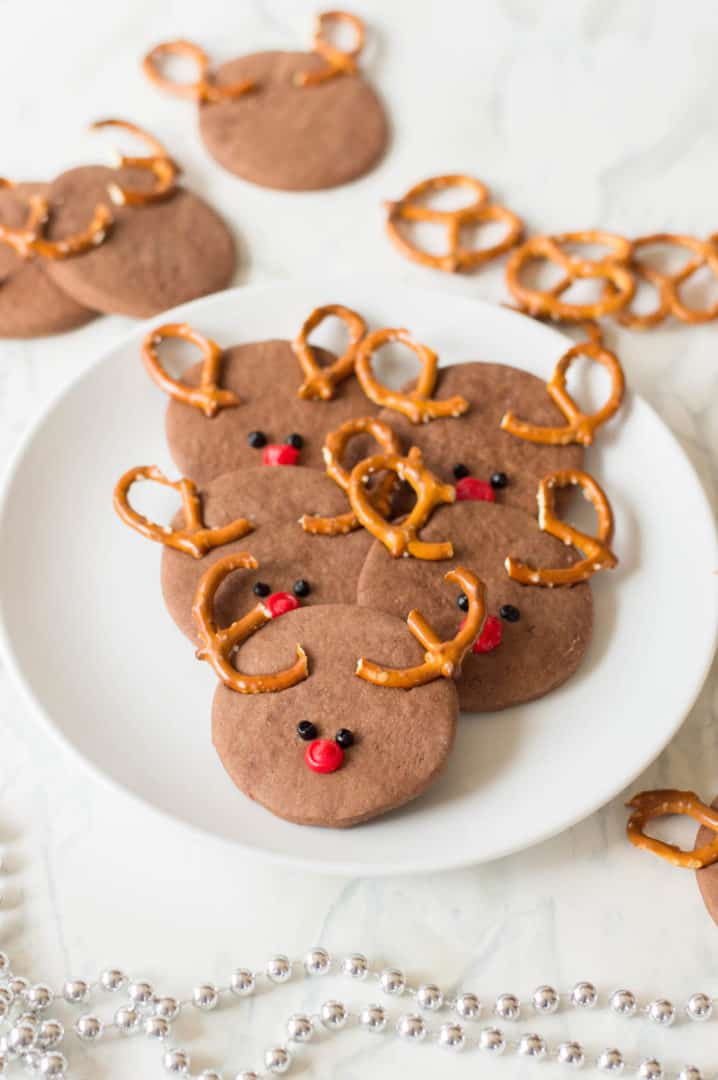 Reindeer cookies on a white plate with extra cookies in the background.