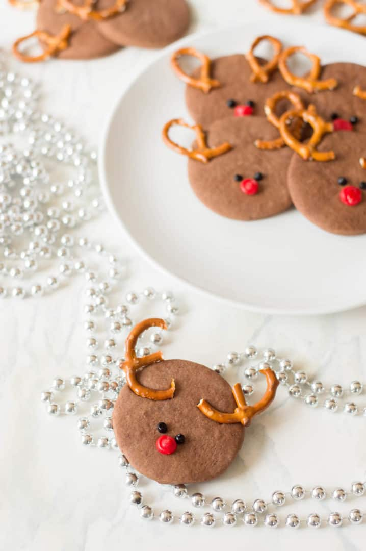A close up of reindeer cookies with a string of silver pearls on the table.