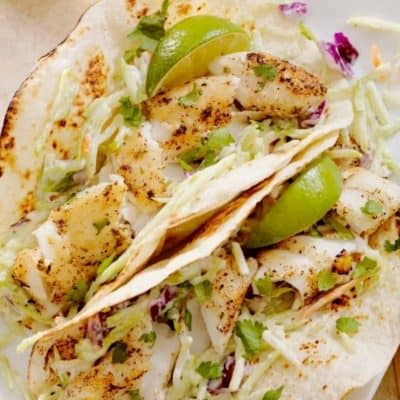 Tilapia fish tacos in crispy shells with lime wedges