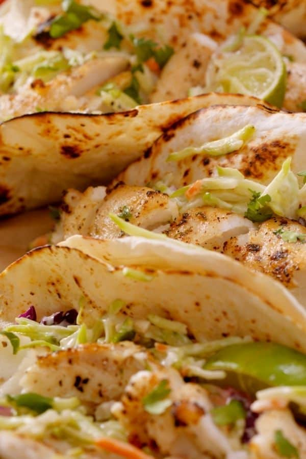 a plate of tilapia fish tacos with lettuce