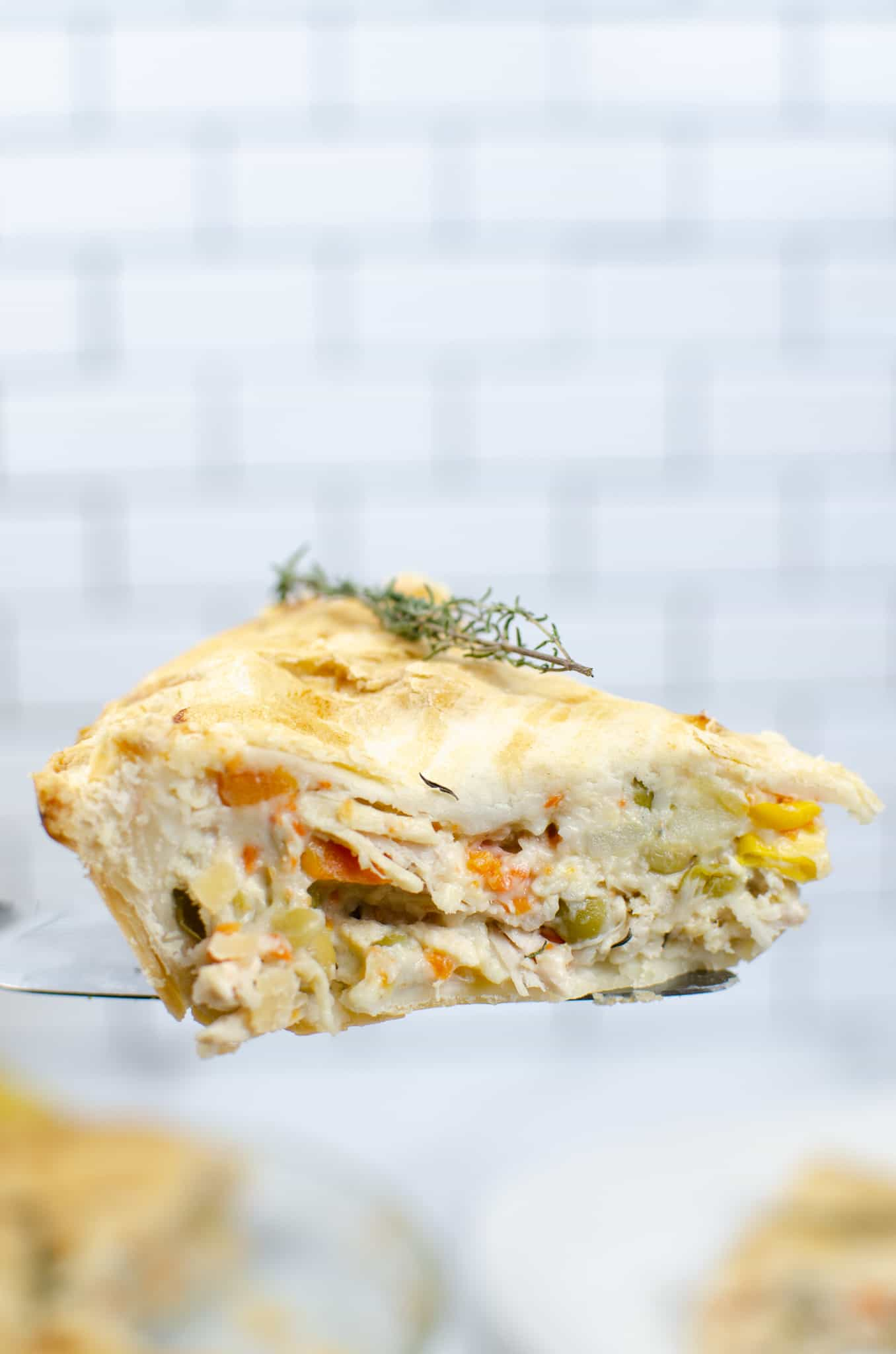 Slice of Turkey Pot Pie held up in a white tile background