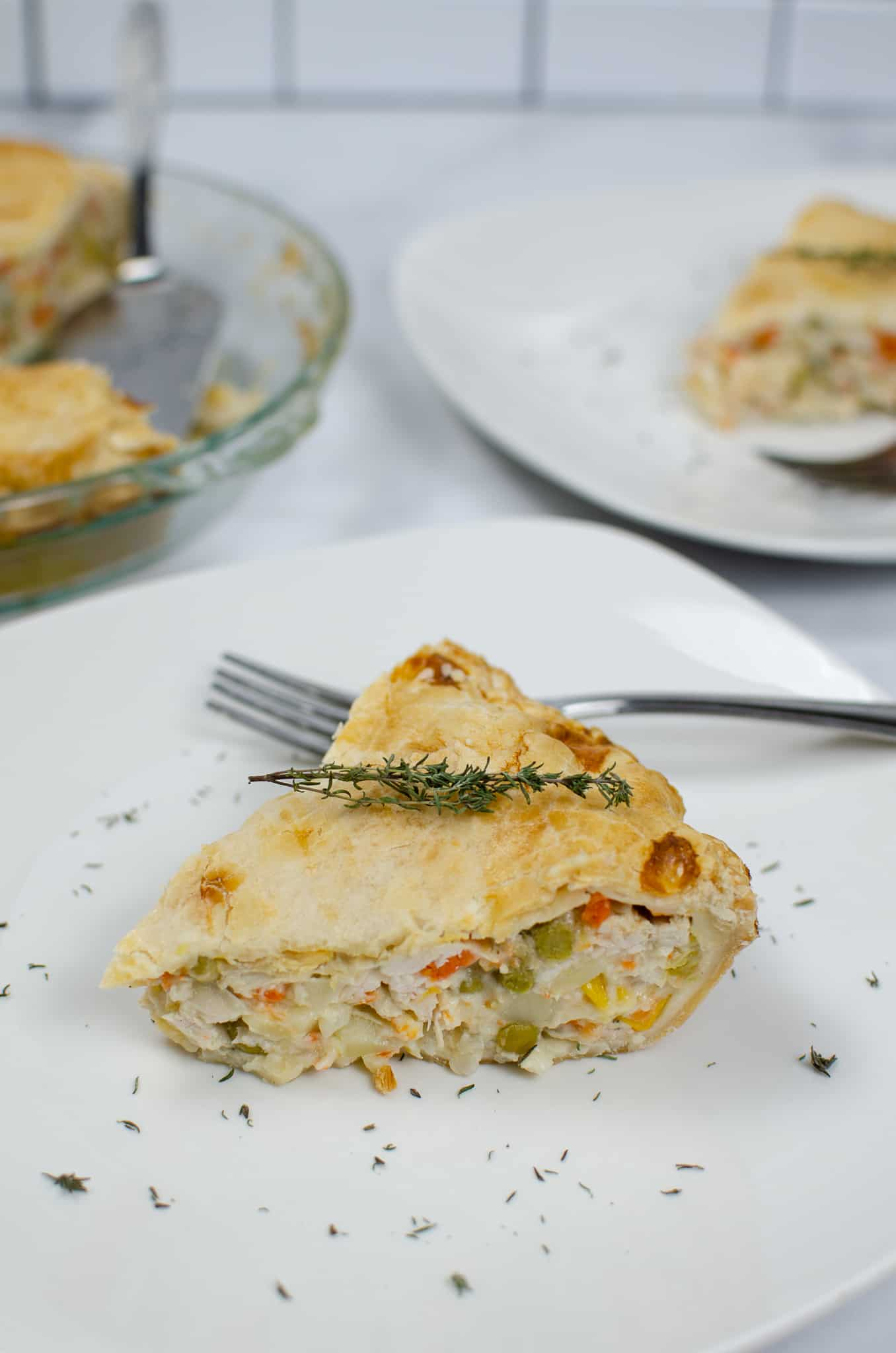 Plate with Turkey Pot Pie with fork and sprig of thyme