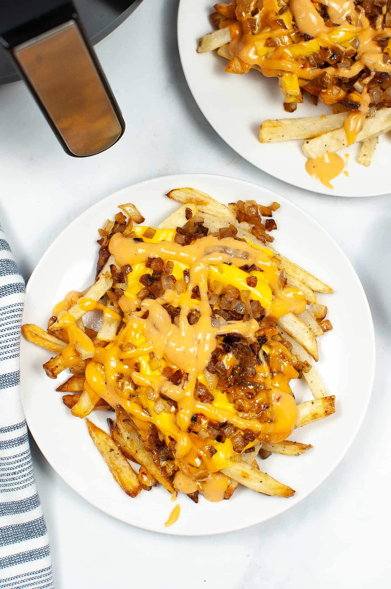 Air-Fryer-In-n-Out-Animal-Fries on a white plate next to an air fryer