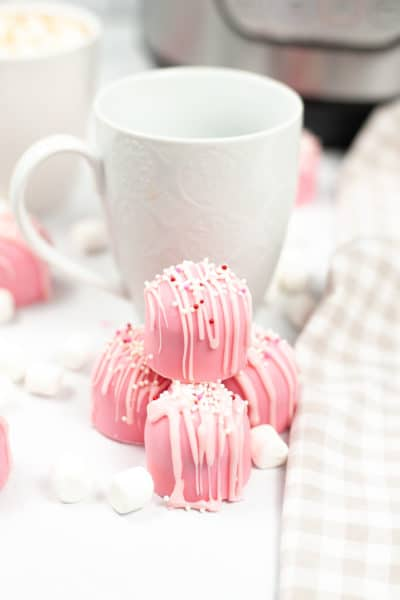 Pink Cupid Hot Cocoa Bombs with a white mug in the background