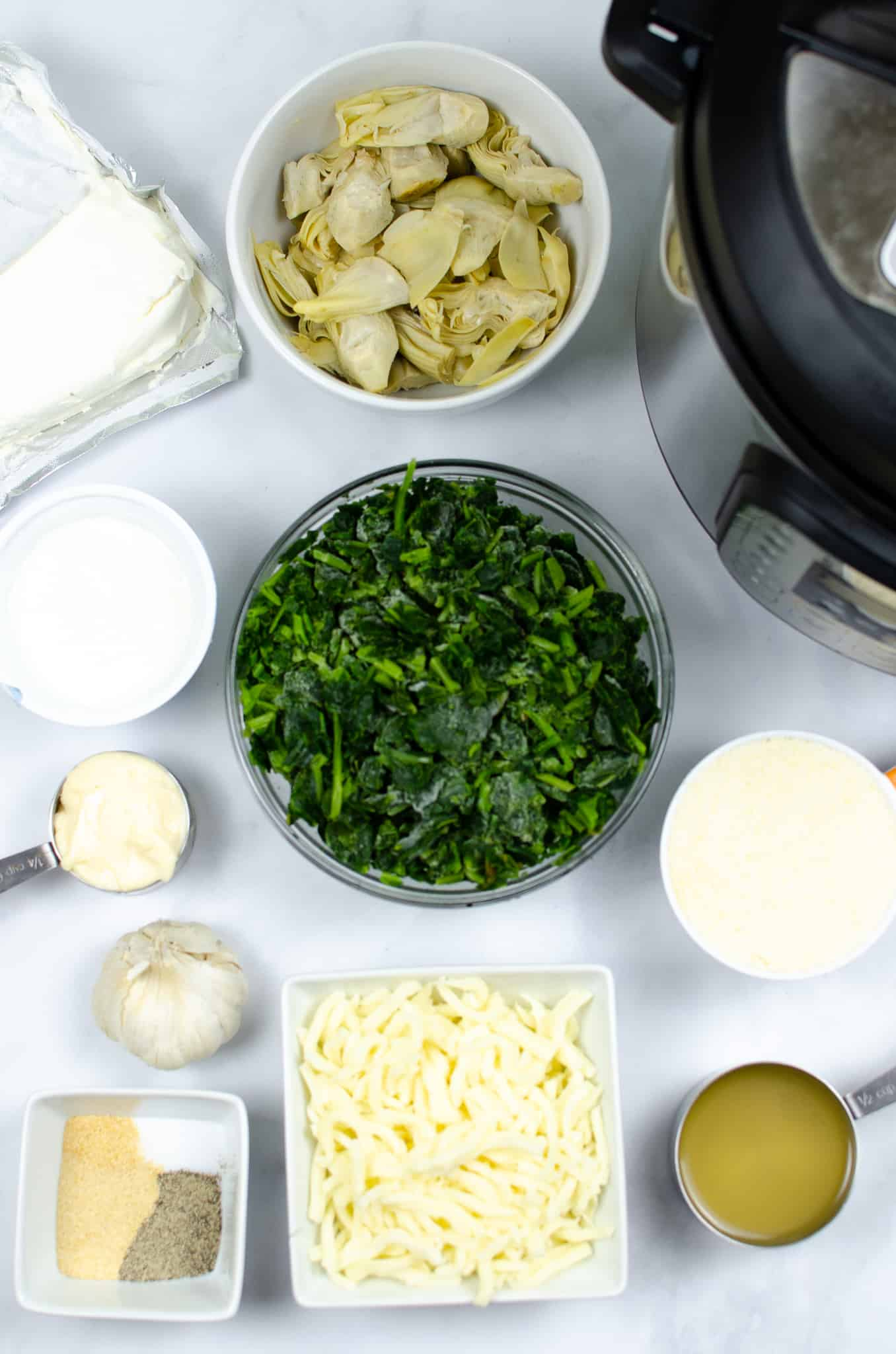 Bowl of spinach, artichoke, cheese and other ingredients for spinach artichoke dip