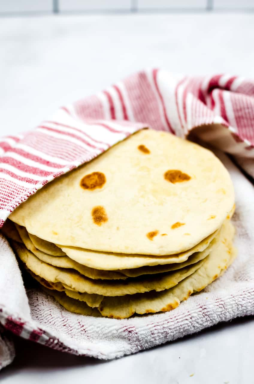 Homemade flour tortillas wrapped in a red and white towel