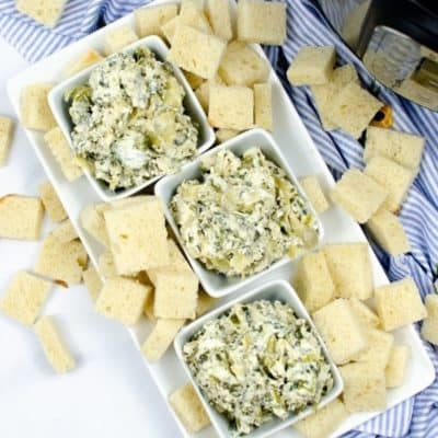 Three white bowls of Spinach artichoke dip surrounded by crackers
