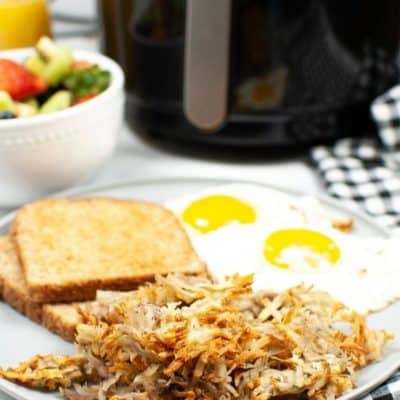 Air Fyer hasbrowns on a white plate with eggs and toast with fruit and air fryer in the background