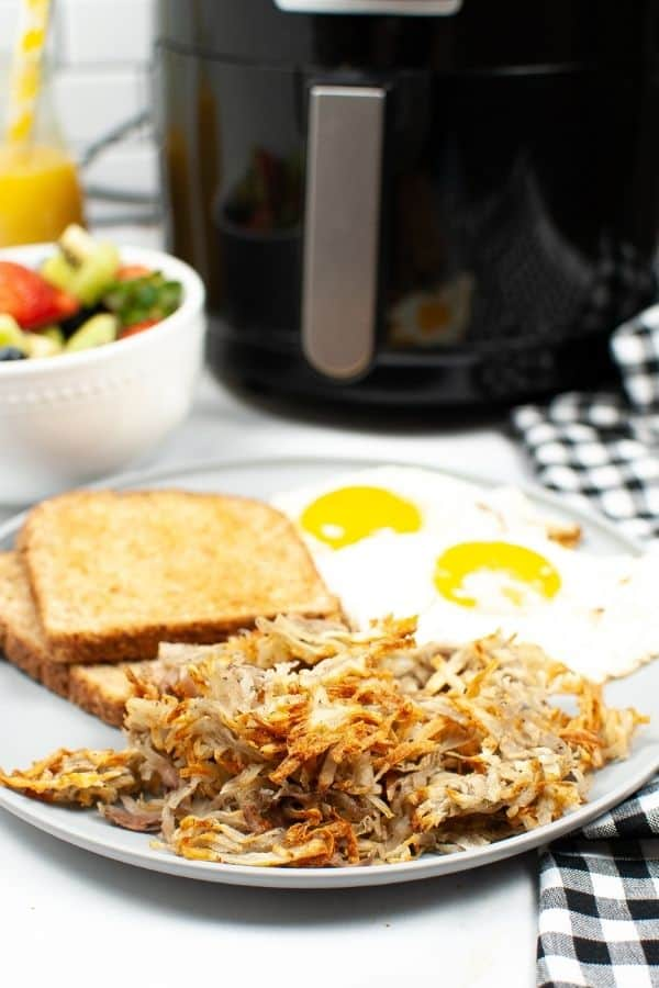 Air Fryer hashbrowns on a white plate with eggs and toast with fruit and air fryer in the background