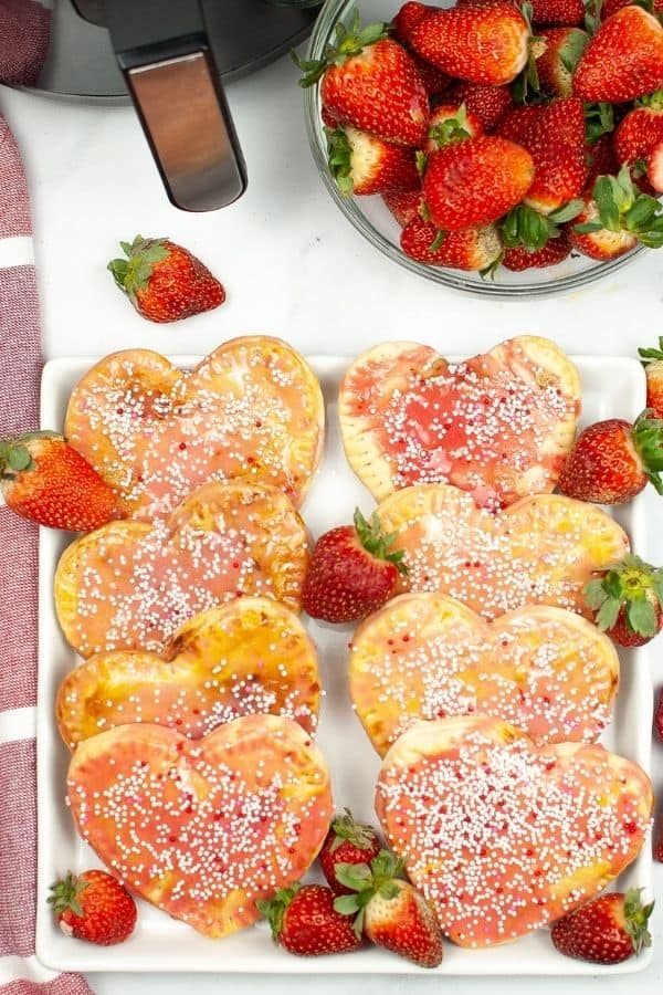 Plate of air fryer pop tarts with fresh strawberries in the background