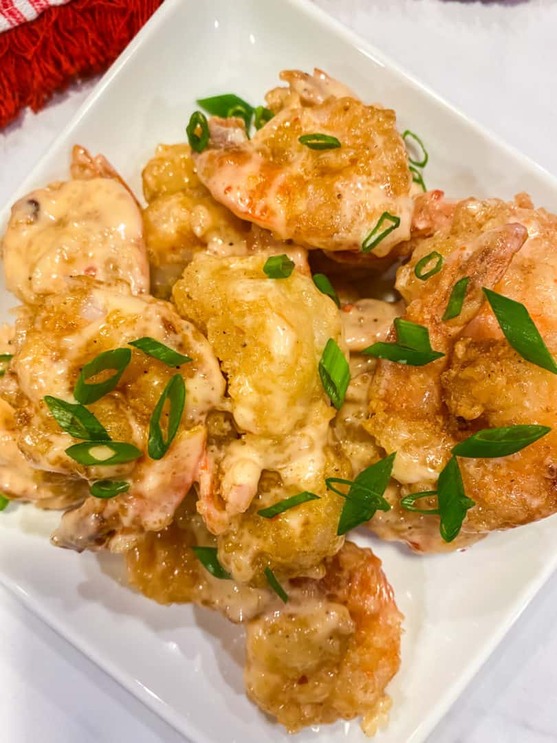 Bang bang shrimp recipe on a white plate with chopped green onions
