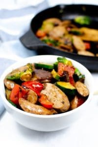White bowl of Chicken Apple Sausage and vegetables with skillet in background
