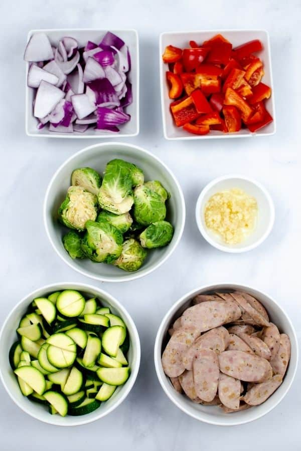 top shot of white bowls filled with sausage, vegetables and seasoning