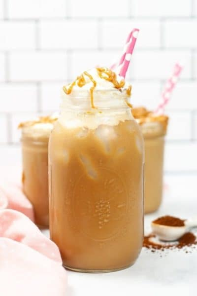 Picture of Iced Caramel Macciato in ason jar with pink straw with others in background