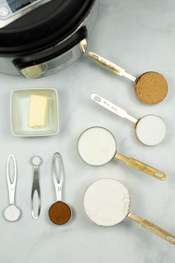Measuring cups and spoons with flour, sugars, butter and ingredients to make churro bites