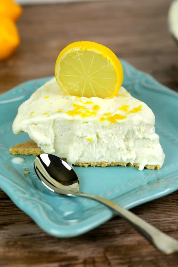 No Bake Lemon Ice Box Pie on a Turquoise dish with a silver spoon and a slice of lemon on top