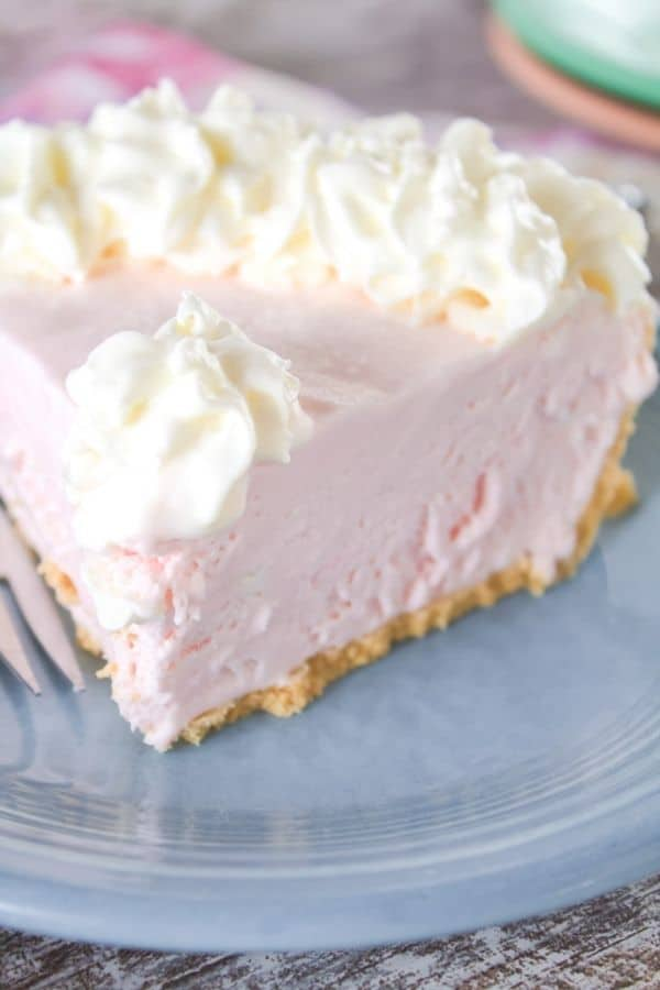Slice of pink lemonade pie on a blue plate with a fork.