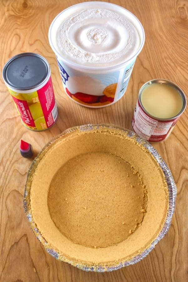 Pie shell surrounded by lemonade, cool whip and sweetened condensed milk