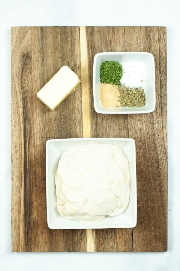 White plate with dough, seasoning and butter on wooden cutting board