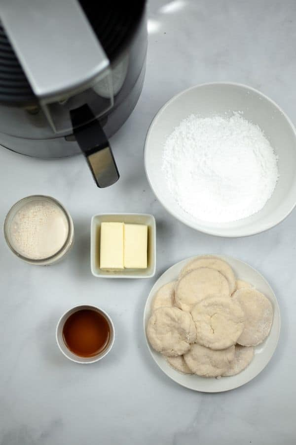 Air Fryer with biscuits, sugar cream and butter all on white plates and bowls
