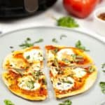 air fryer margherita pizza cut in 4 slices on a wite plate sprinkled with fresh herbs