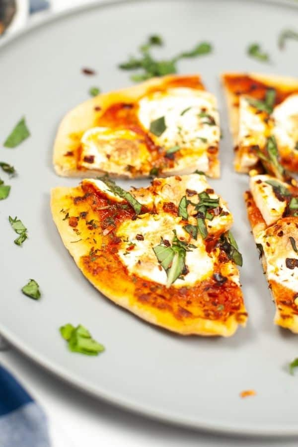 Cut up pizza on a plate with fresh herbs surrounding it