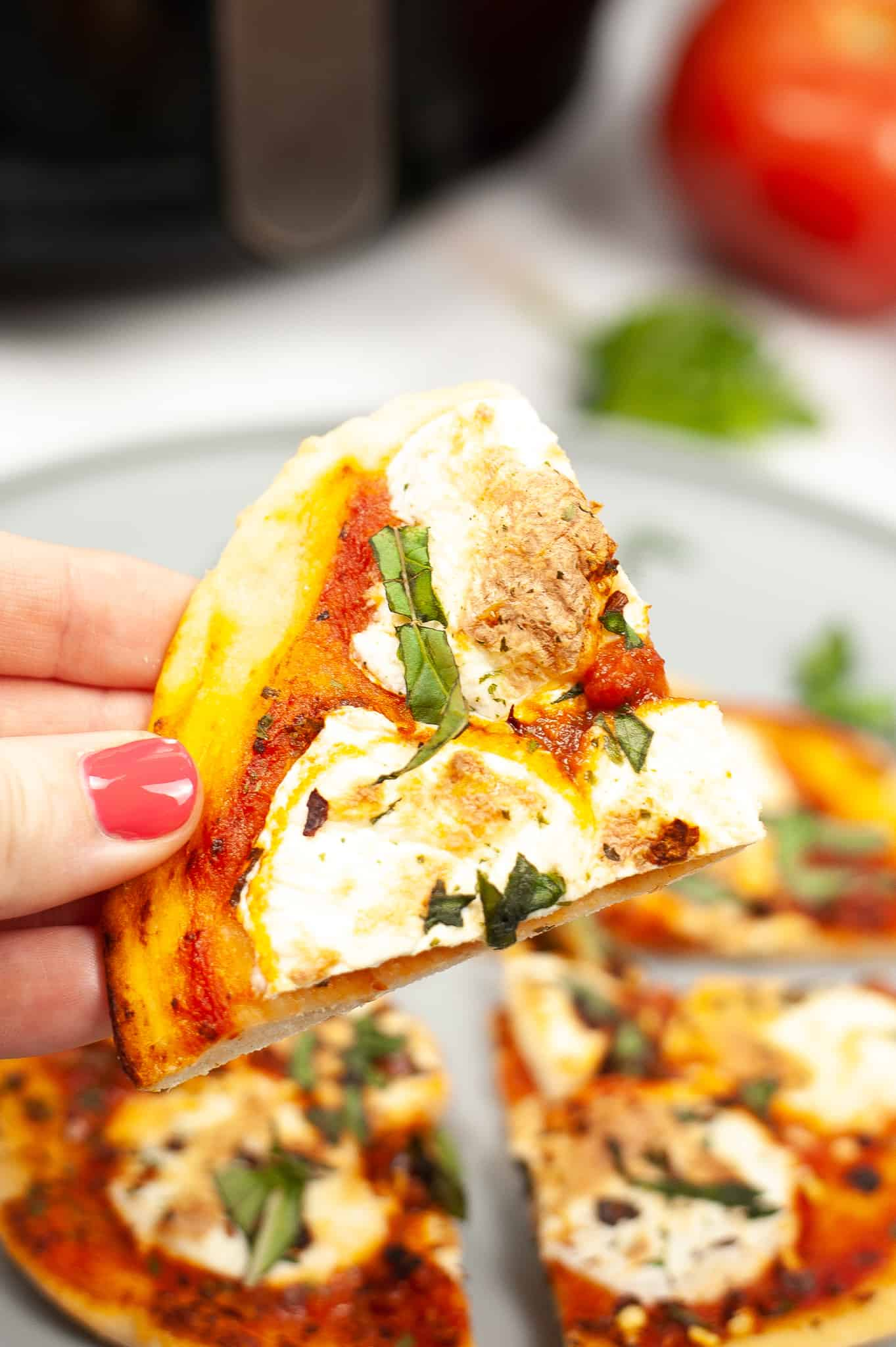 close up slice of air fryer margherita pizza in someone's hand