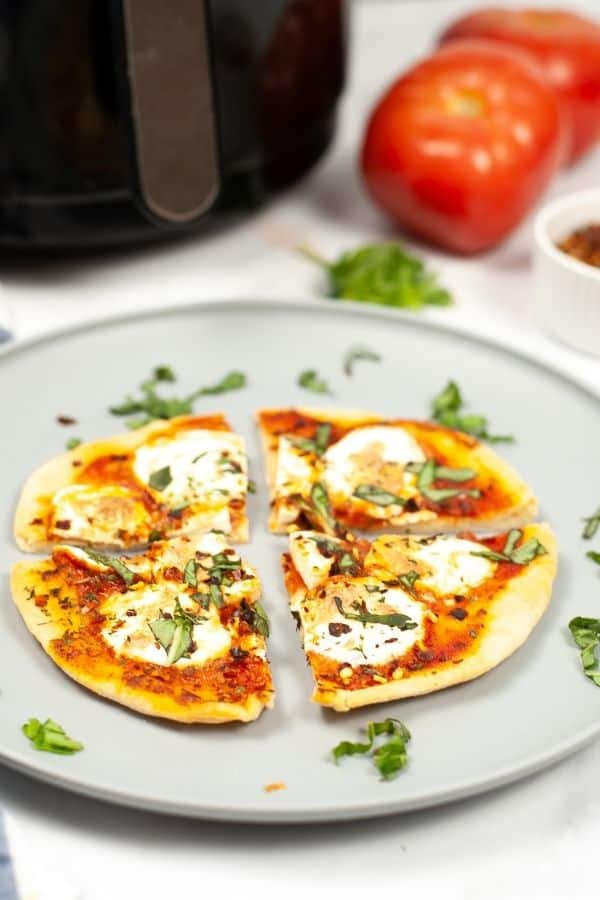 air fryer margherita pizza cut in 4 slices on a white plate sprinkled with fresh herbs