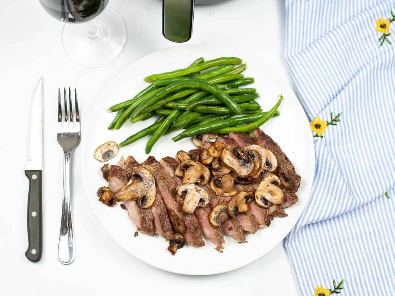 Cooked steak on a white plate with cooked mushrooms and green beans with a fork, steak knife and blue and white stripped napkin.
