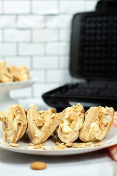 4 banana pudding tacos with waffle iron in the background