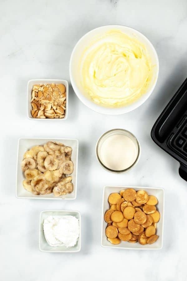Dishes of banana slices banana pudding, vanilla wafers and waffle mix.