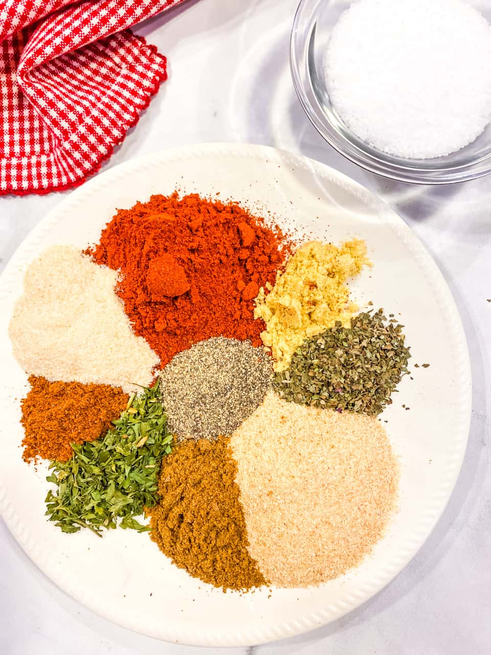 All the spices needed for the spice blend on a white dish