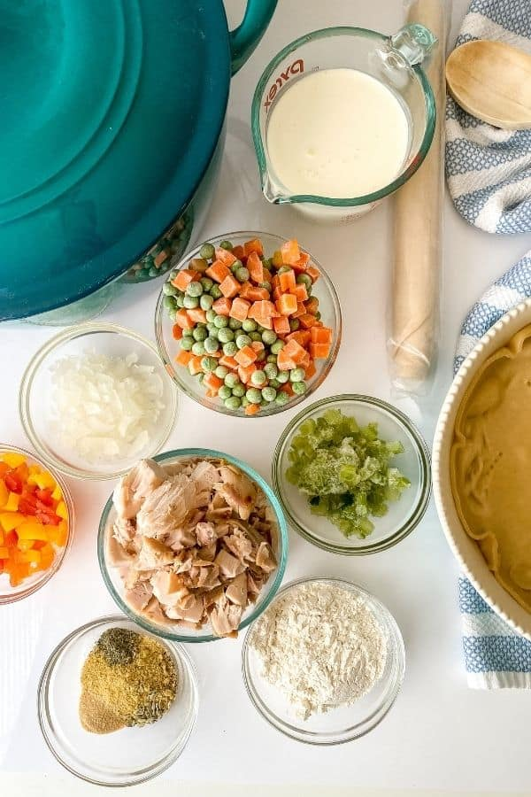Glass dishes filled with chicken, peas and carrots, pie doough and other ingredients required for chicken pot pie